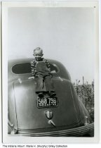 Image of Boy sitting above license plate on a Desota, Wabash, Indiana, 1940 - Lowell Dean Gilley, son of Clinton M. and Marie (Murphy) Gilley sitting atop the family's Desoto automobile. The image is date October 13, 1940.