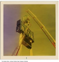Image of Installation of the First National Bank sign, Indiana, ca. 1955 - A man from Johnson Brother Sign Company is standing on top of a tall ladder. He is guiding the top of the 1st National Bank sign (held by a crane) into place.