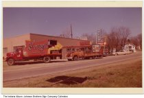 Image of Johnson Brothers Sign Company and trucks, Indiana, ca. 1960 - Trucks belonging to the Johnson Brothers Sign Company of South Whitely, Indiana, are seen transporting signs for a Shoney's Restaurant. The sign for the Johnson Brothers Sign Company is seen in the background.