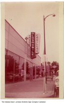 """Image of Cadillac and Oldsmobile dealership, Warsaw, Indiana, ca. 1955 - A bench can be seen in the background that reads """"Courtesy City of Warsaw,"""" as well as a DX gas station. This view looks north on Lake Street toward the West Main Street intersection."""