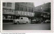 Image of Hill's Furniture store, Fort Wayne, Indiana, ca. 1950 - The Johnson Brothers Sign Company truck is parked in front of the store, as is a truck for Minear Electric. Nearby stores include Kuttner's Mens Wear, a cafe, and a typewriter store. Businesses in the 1100 block of South Calhoun Street in the 1949 Fort Wayne city directory are the Palace Cafe restaurant (1136), Parkerson's Typewriter Sales (1130), and Kuttner's Men's Wear (1126-1128).