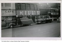 Image of Work on the Hill's Furniture store sign, Fort Wayne, Indiana, ca. 1950 - The Johnson Brothers Sign Company truck is parked in front of the store where they are installing the sign. Nearby stores include Kuttner's Mens Wear, a cafe, and a typewriter store. Businesses in the 1100 block of South Calhoun Street in the 1949 Fort Wayne city directory are the Palace Cafe restaurant (1136), Parkerson's Typewriter Sales (1130), and Kuttner's Men's Wear (1126-1128).