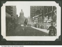 "Image of Douglas ""Wrong Way"" Corrigan parade on West Market Street, Indianapolis, Indiana, 1938 - Captioned ""Very Beginning of hte Parade."" View looks west on West Market Street at a color guard with the Indiana Statehouse in the background. Other snapshots in the series reveal that this is a parade for Douglas ""Wrong Way"" Corrigan and the ""Indianapolis Star"" states that he was in an Indianapolis parade on August 19, 1938 as part of his goodwill tour through the country. Nearby businesses include Tavel's Jewelry, Wheeler's Lunch, Holland's Lunch, and Lorenz Music Store. From a photo album compiled between 1935 and 1938 by Lee Wayne Dickey (1919-2003)."