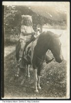 Image of Alice Weghorst on a pony, Indianapolis, Indiana, ca. 1924 - Alice Weghorst (later May, 1919-2014) rides a pony in the yard of her home at 33 East 34th Street in Indianapolis. The pony was the prop of an itinerant photographer.
