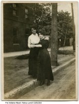"""Image of Ella Roney and a friend on Talbott Street, Indianapolis, Indiana, ca. 1915 - Nancy Elsa """"Ella"""" Roney (left) is seen with a friend of hers near the Cole Auto Company where she worked as a operator."""