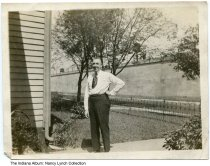 Image of John Roney at his parents' home, Indianapolis, Indiana, ca. 1920 - John Roney is seen in front of his parents' home on South Talbott Street. In the background are the elevated train tracks for the Pennsylvania Railroad.