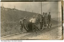 Image of Men working on railroad, Indiana, ca. 1920 - Four men are seen standing on a railroad track with a handcar and a large spool of cable or wire.