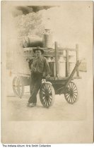 Image of Man standing with a transfer wagon, Indiana, ca. 1915 - A man is leaning on a large transfer wagon holding a large trunk and milk cans.