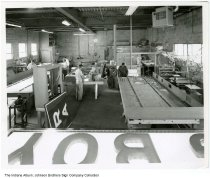 Image of Workers inside Johnson Brothers Sign Company, South Whitley, Indiana, ca. 1960 - Six employees are seen inside the facility at work making signs.