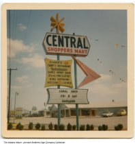 Image of Central Shopper's Mart sign, Wabash, Indiana, 1965 - This photo is timestamped Aug 65, and shows Miller Furniture in the background. Businesses include Clark's IGA, Terry's Restaurant, Gackenheimer's, Dick's for Clothes, King Hipskind [hardware], and Auto Clean Car Wash.  [The black and white version of this image was timestamped August 1965, and can be seen at ia-0184-0168.]