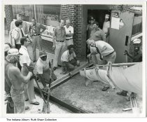 Image of Mayor Bill Hudnut observing work on East 10th Street, Indianapolis, Indiana, ca. 1980 - Mayor Hudnut assisting workers pouring a sidewalk in front of a bar on East 10th Street.