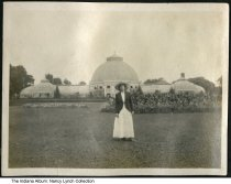 """Image of Ella Roney at a park, Indianapolis, Indiana, ca. 1915 -  Nancy Elsa (""""Ella"""") Roney is seen standing before a large greenhouse in a park."""