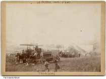 """Image of Threshing at Saint Peter, Indiana, ca. 1905 - A group of men are seen operating a threshing machine near a barn. It is captioned """"St Peters Ind. views / Thrashing."""""""