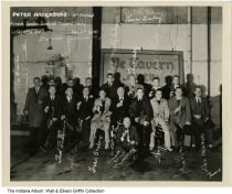 """Image of Purdue Senior Football players at a brewery, Lafayette, Indiana, 1936 - The caption reads """"Peter Anderson's 4th annual Purdue Senior Football Players Party, Lafayette Indiana, Dec. 5th 1936"""", and is autographed by the players. Included are Leon Bailey, Dutch Fehring, Lee Grauls, Louis Pauttie, Ted Fehring, Tommy Withers, Fred Stoleup, Uncle Doc Anderson, Wes Hickman. They are in the Rathskeller room at the Lafayette Brewery, and are seated in front of a Ye Tavern sign."""