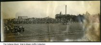 Image of Marching band on football field, Lafayette, Indiana, ca. 1910 - This panoramic view photo shows spectators watching a football game, and a marching band on one end of the field. There are large buildings in the background. This is from an album from Lafayette Indiana, so it might show a Purdue University football game.