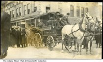 "Image of Police patrol wagon, Lafayette, Indiana, ca. 1905 - A group of people are seen standing around a horse-drawn Police Patrol wagon. People re looking out the window from a building with signs for ""The Metropolitan"" and ""American Laundry Cleaning Co."". 