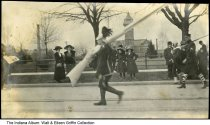 Image of Man with a large rifle in a parade marching band, Lafayette, Indiana, ca. 1910