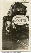 "Image of Ford dealers train, Indianapolis, Indiana, ca. 1940 - An unidentified man is standing by a train engine with a sign reading ""Indianapolis Branch Ford Dealers."""