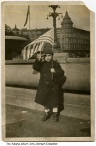 """Image of Boy posing near the English Hotel, Indianapolis, Indiana, November 11, 1918 - Meredith E. Caldwell (b. 6/16/1914) is seen holding an American flag and saluting. The English Hotel is seen behind him on Monument Circle. The photo was taken on """"Victory Day,"""" November 11, 1918."""