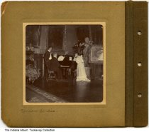 Image of Nellie Simmons Meier in France, 1904 - This photo shows Nellie Simmons Meier on the right, leaning on a piano.