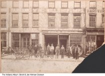 """Image of Fred Reule, Fairbanks WIndmills and Pumps, Tippecanoe County, Indiana, ca. 1900 - Eleven men are seen standing in front of a business that sold plows and other farming implements and supplies. On the building is written """"Fairbanks Wind Mills and Pumps, Engines, Threshers, Planters, Matchless Clover Hullers, Superior Drills, Cultivators, Harrows, Jones Lever Binders Mowers Fred Reule"""". A hardware store is next door."""