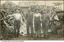 Image of Simon Cook salvage yard, Wabash, Indiana, ca. 1900s - Simon A. Cook (far left) and the son of Simon Frank Cook (far right) are seen in the Cook salvage yard that was started by the donor's great-grandfather Cook (who also built the Cook building, still standing as of 2016). The salvage business was sold in the 1920s.