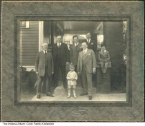 """Image of Family at the home of Bess (Cook) Kallmyer, Muncie, Indiana, ca. 1925 - Children and grandchildren of Solomon and Fanny Barrett are gathered at the home of Bess (Cook) Kallmyer. The children are David """"Butch"""" Kallmyer (standing), and David Moie Cook (seated at right. The men are (L-R): Simon A. Cook, Sol O. (or Ben) Cook, Moie Cook, David Kallmyer, Ben (or Sol) Cook."""