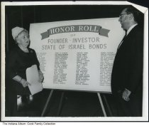 Image of Sarah Goodman and David Moie Cook, Indianapolis, Indiana, ca. 1950 - They are standing before a list of and Honor Roll for Founders and Investors for the State of Israel Bonds.