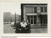 Image of Soldiers and woman in front of the the Barnes Hotel, Indianapolis, Indiana, ca. 1943 - Two men in uniform and a woman wearing a fur coat stand near the Barnes Hotel. The building is on the southeast corner of McCrea Street and West Jackson Place. Shown in the distance are commercial buildings on South Meridian Street.