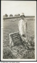 Image of Child by gravestone of Keith Bringle, Indiana, ca. 1928 - A girl of about six years of age stands by a grave marker for Keith Bringle (b. August 23, 1923 - d. February 28, 1928). The tombstone is located in Liberty Cemetery, Groomsville, Indiana, Tipton County.  The girl is identified on the back of the photo as Thelma Arretha Edwards.