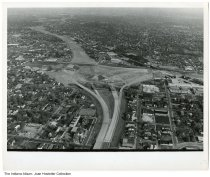 Image of Aerial view of I-65 and I-70 highway construction, Indianapolis, Indiana, ca. 1970 - This aerial photo by Indianapolis Star staff photographer William A. Oates is stamped October 27, 1974. The Central Avenue Methodist Church is seen lower left. The Coca Cola Building school bus depot is at the far right in the center.   Other references images show construction beginning in 1969 or 1970, so the stamp may not reflect the exact date of when the photo was taken.
