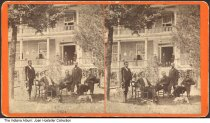 """Image of Men seated outside of Wernle Orphans' Home, Richmond, Indiana, ca. 1885 - Five men are in front of a building; a group of children and women are on the porch. Written on the back of the card is """"Wernle Orphans Home."""""""