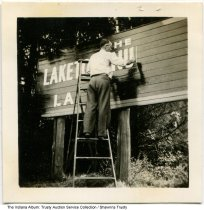 Image of Man painting Laketon Nurseries sign, Laketon, Indiana, 1935, ca.  - Lyle Reith is seen painting a large wooden sign for Laketon Nurseries.