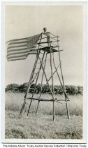 Image of Child on a makeshift lookout tower with a flag, Indiana, ca. 1935   - Part of the Reith family albums, so the child may be Robert Reith.