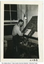 Image of Lyle Reith painting a small sign, Marion, Indiana, ca. 1940