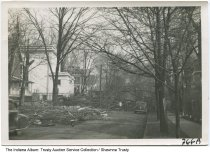 Image of Storm damage on a residential street, Marion, Indiana, ca. 1940 - Several people inspect downed trees on a residential street that has several large houses. From a photo album owned by the Reith family of Marion, Indiana.