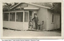 """Image of Reith family at Lake Tippecanoe, Kosciusko County, Indiana, ca. 1935 - A man and a boy carrying a pail are seen in front of """"Marione,"""" a cabin on Lake Tippecanoe owned and built by the Reith family of Marion, Indiana."""