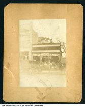 """Image of Carriage in front of King's Steam Laundry, ca. 1900 - Several people are standing in front of the King's Laundry building. An awning over the door reads """"King's Steam"""". The horse-drawn delivery carriage in front shows a phone number of """"123"""", and an address that is at (?) and 5th Streets."""