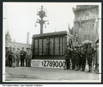"""Image of World War I bonds sales display on Monument Circle, Indianapolis, Indiana, 1918 - Men in soldiers' uniforms are standing by a display on the north side of the Soldiers' and Sailor's Monument that reads """"The War Chest Fund contains Today $2789000."""" Dated May 28, 1918."""