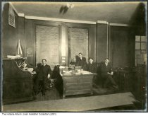 Image of Four men in an office, Central Union Telephone Company, Indianapolis, Indiana, 1907 - Another photo in this bound album shows a calendar dated December 1907.  The calendar in this image is from Massachusetts Mutual.