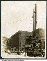 Image of Capitol Transfer Co. at Gem Laundry building, Indianapolis, Indiana, 1922 - This image shows several men on the roof of Gem Laundry, two of whom are climbing up a large pipe. They appear to be lifting another pipe into place. The Colonial Theatre at 113 West New York Street is seen next door, and a sign for Cut Rate Drugs - Pearson Drug Co. is on the corner.  The Indiana licence plates on the cars are for 1922.