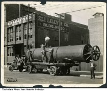 """Image of Capitol Transfer Co. at an Eli Lilly building, Indianapolis, Indiana, 1923 - Seven men are by a truck owned by Capitol Transfer Co. that is holding a large pipe or piece of machinery. The truck is parked in front of Eli Lilly Building Number 20. It reads """"34,000 lbs."""" in the lower left."""