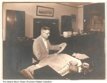 """Image of Man in office by Illinois Central map looking at papers, ca. 1940 - The glass on the window in the background reads """"Systems."""""""