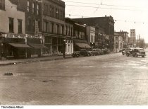 Image of View of shops in downtown Greensburg, Indiana, ca. 1940 - Downtown Greensburg along Broadway Street from Main Street. Shops seen are Leader Shoe Store and Batterton's Drugstore.