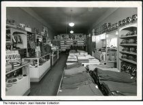 Image of View inside Houck's Mens and Boys Wear, Williamsport, Indiana, ca. 1948 - Store owner Joseph M. Houck is seen in his store by a counter holding accessories. Hats line the wall on the right, and there are tables holding trousers in the center.