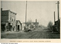 Image of Prospect Street looking east from Virginia Avenue, Indianapolis, Indiana, ca. 1889 - Some of the businesses seen are P. M. Koenig Dry Goods, C. H. Wehling Shoeing and Gneeral Blacksmithing, H. Mitschrich (?) Flour and Feed, a shop for glass and tinware, and a church.