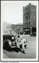 Image of Man seated on the bumper of his car, Indianapolis, Indiana, ca. 1940 - A man is seen sitting on the bumper of a car with Indiana plates in a commercial area of town. Across the street is a vacant building listed by W. A. Brennan, an Indianapolis realtor.
