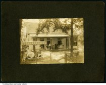 Image of Family at home by a photographer from Terre Haute, Indiana, ca. 1900 - Three women are seated on a porch of a small house, and two young women are seated in a two-seat glider just inside the fence.