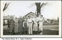 Image of Elmer Streidelmeier and family, Columbus, Indiana, 1936 - Elmer Streidelmeier (man in the light colored clothing in the front) and his wife (holding a baby, to Elmer's left) owned an operated the DX service station and restaurant at the Columbus Airport. The photo is dated April 12, 1936. At the far right is Dorothy (Johnson) Mundt holding her daughter, Shirley. Dorothy's husband Alvin is the man behind her wearing a hat.