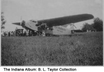 """Image of Plane owned by Reg Robbins at Columbus, Indiana airport, ca. 1936 - A group of people are seen around a plane marked """"Reg Robbins, Fort Worth."""""""